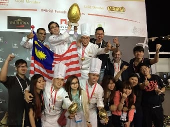 The winning Asian Pastry Cup 2014 team of (front row 3rd and 5th left respectively) Chef de Partie Tay Chee Siang of the Kuala Lumpur Convention Centre and Pastry Chef Tan Wei Loon and (top row, 3rd left) Executive Pastry Chef Chiam Ko Seen from the Academy of Pastry Arts Malaysia, together with Chef Chern Chee Hong, President of Chefs Association of Malaysia, and their assistants and supporters give their victory the thumbs up.