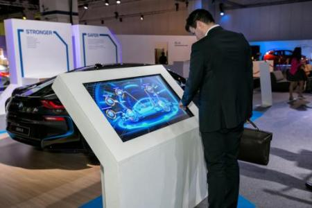 A visitor explores the BMW i8's features via an X-ray touch-screen panel at the Future of Mobility zone