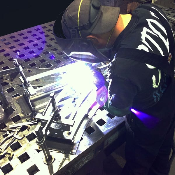 A welder creating a custom TK6 truss curve section.