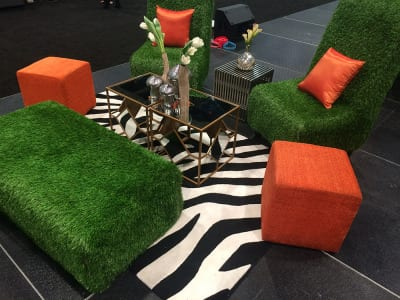 """A zebra print rug and gold coffee table offset the """"lawn"""" chairs."""