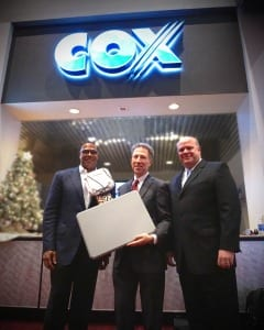 Cox President Pat Esser (center) displays one of 2,000 access points deployed by Cox Business throughout LVCC. Esser is joined by Cox Business SVP Steve Rowley (right) and Cox Business/Hospitality Network Vice President Derrick Hill.