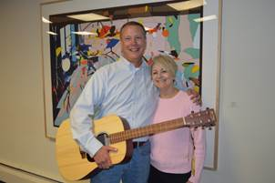 President and CEO Deb Archer (Greater Madison Convention & Visitors Bureau and Madison Area Sports Commission) stands with Jeff Holcomb Senior Convention Sales Manager at his celebration of 20 years of excellent work. Holcomb is holding a guitar, gifted to him by the organization, as Jeff a hobby musician has been known to use all of his skills—including his considerable songwriting talents to help groups.