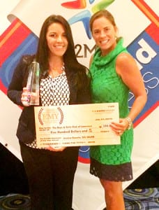 EMY Winner Jessica Gauvin (left) is presented with her check and trophy from The Expo Group's Creative Director Nicole O'Leary